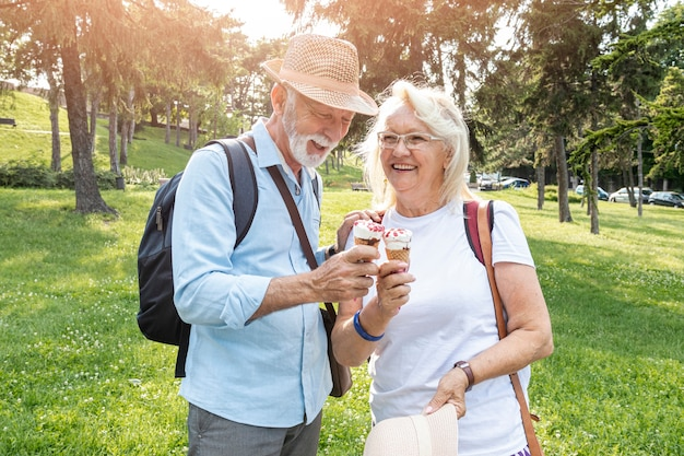 Elderly couple holding ice cream in hand