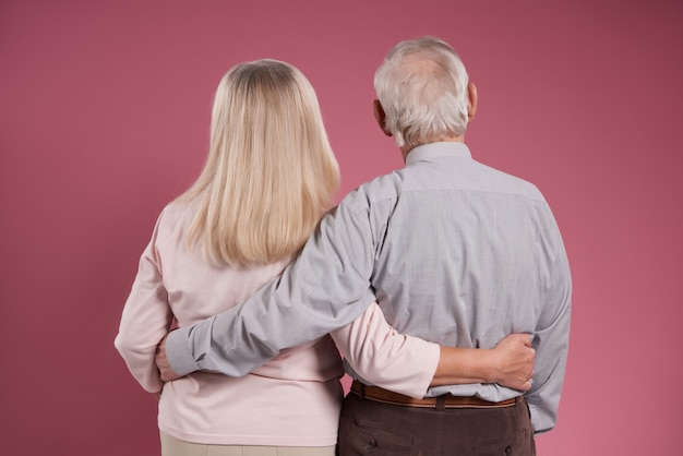 Elderly couple hugs each other from back.