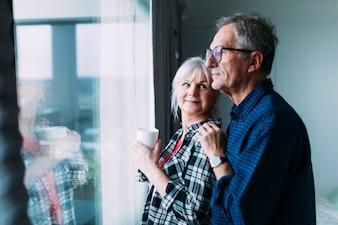 Elderly couple in retirement home in front of window