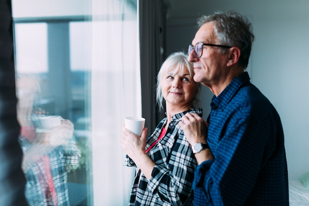 窓の前に退職の家の高齢者のカップル