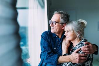 窓から見える退職の家の高齢者のカップル