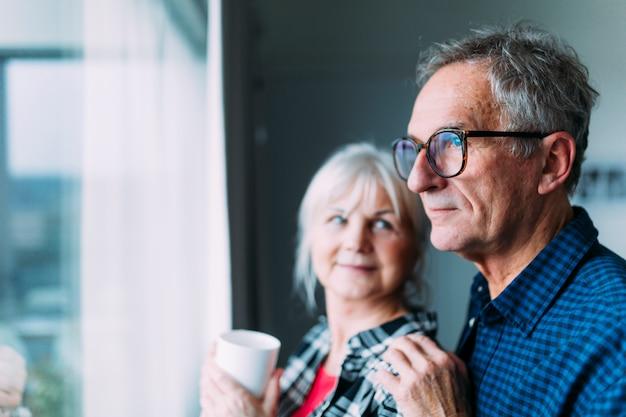 窓の隣に退職の家の高齢者のカップル