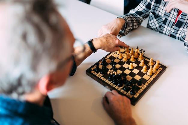 Пожилая пара в отставке домой, играя в шахматы