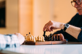 Elderly couple in retirement home playing chess