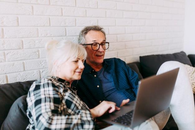 ラップトップを使用している退職家の高齢者のカップル