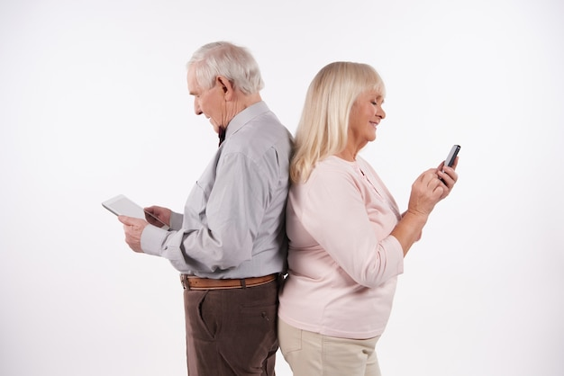 Elderly couple interact with smartphones.
