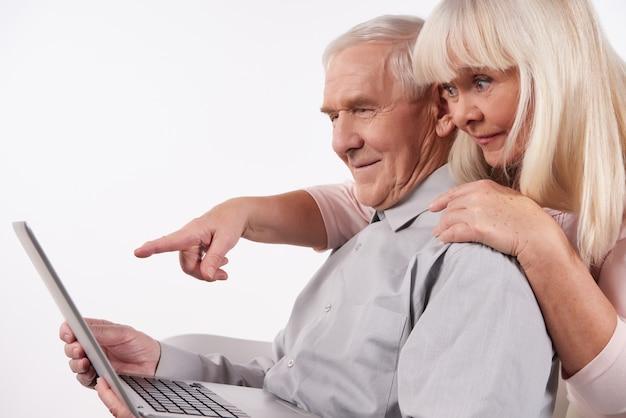 Пожилая пара взаимодействует с ноутбуком.