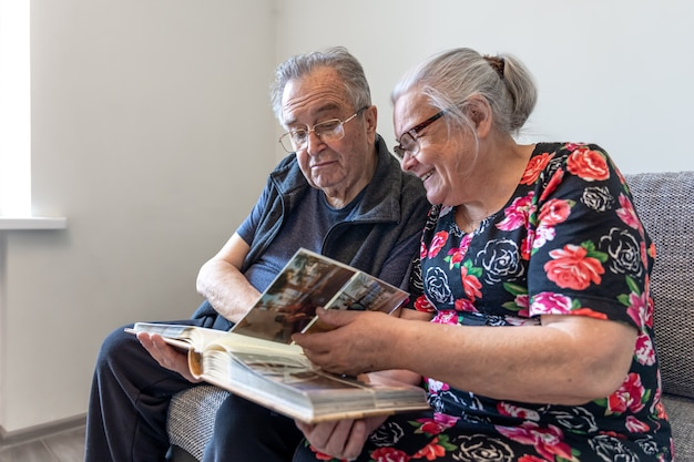 An elderly couple is looking at photographs in a family photo album.