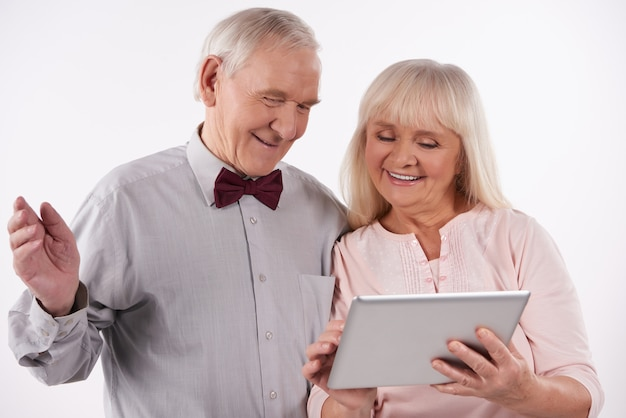 Elderly couple is looking at something on computer tablet.