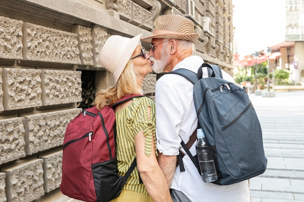 Elderly couple kissing on the street