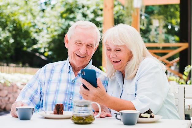 Пожилая пара смеется, глядя на смартфон
