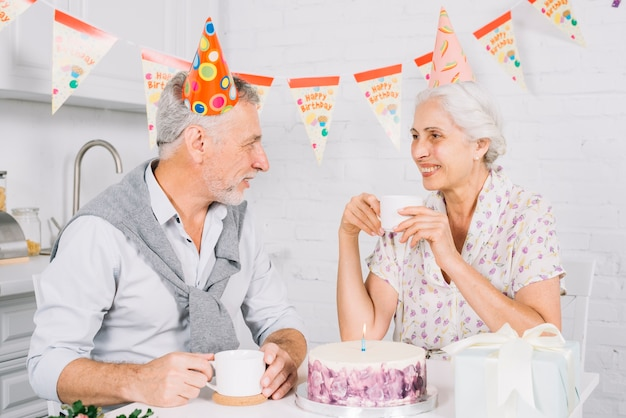 Пожилые пары смотрят друг на друга, имея чашку кофе во время вечеринки по случаю дня рождения