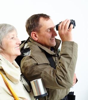 Elderly couple looking through binoculars