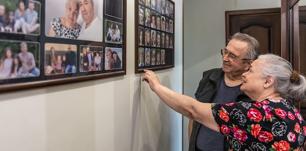 An elderly couple looks at family photos on the wall and recalls the past.