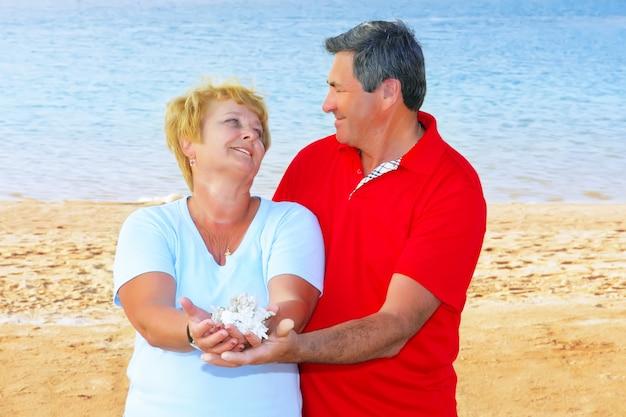 Пожилая пара на побережье, держа в руках ракушки и кораллы.