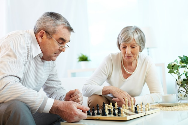 Elderly couple playing chess at home
