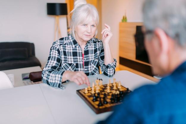 Пожилая пара играет в шахматы в доме престарелых