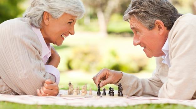 チェスをする高齢者カップル