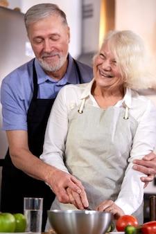 キッチンで野菜サラダを準備している老夫婦、白髪のハンサムな男が妻の料理を手伝い、健康的な朝食をとります。手に焦点を当てる
