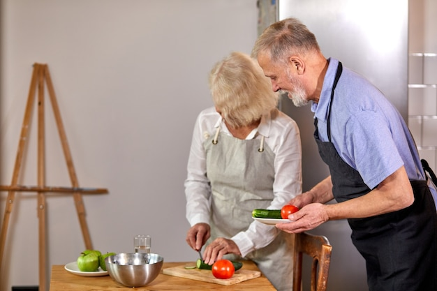 キッチンで野菜サラダを準備している老夫婦、白髪のハンサムな男は、健康的な朝食を食べに行く、料理で妻を助けます