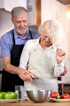 Elderly couple preparing vegetable salad in kitchen, gray-haired handsome man helps wife with cooking, going to have healthy breakfast