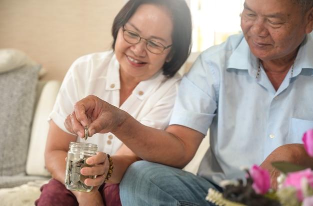 노인 부부는 돈을 절약하기 위해 유리 항아리에 동전을 넣었습니다.
