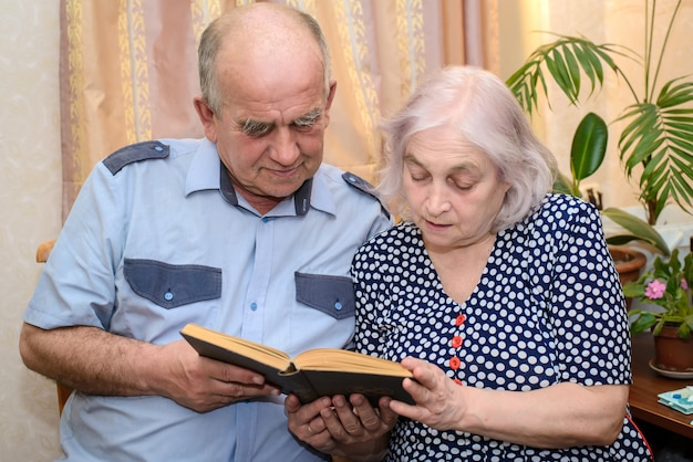 Elderly couple reading a book together at home