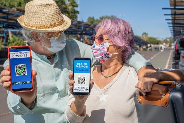 코로나바이러스 예방 접종을 받은 사람들을 위해 디지털 건강 여권을 보여주면서 여행할 준비가 된 노부부. 코로나19 예방접종 모바일 앱