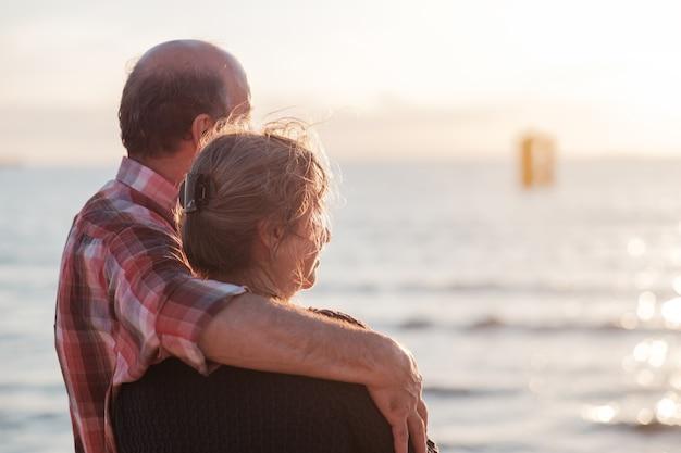 Пожилая пара отдыхает на берегу моря.