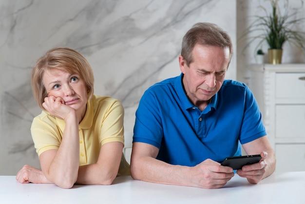 彼女の引退した男性の夫が彼女を無視している間、不幸に見える老夫婦の年配の女性の妻は退屈しています