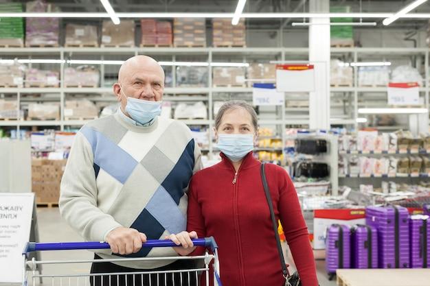 슈퍼마켓에서 쇼핑하고 의료 얼굴 마스크를 착용하는 노인 부부