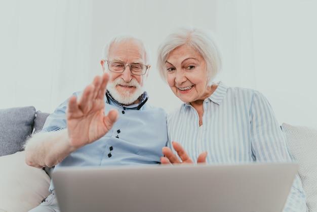 집에서 컴퓨터 노트북으로 인터넷에서 쇼핑하는 노부부 - pc와 소셜 네트워크 앱을 사용하는 아름다운 행복한 노인들