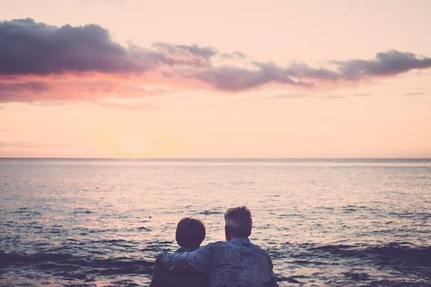 노인 부부 앉아서 일몰 휴식에서 바다를보고 서로 포옹. 휴가, 여가 시간, 휴식의 개념. 포옹과 관계 l 함께 백인 성인 사람들에 대한 사랑