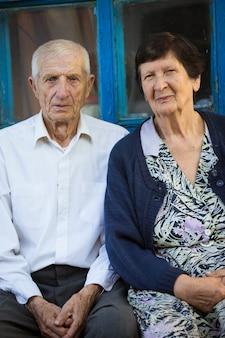 Пожилая пара, сидя перед сельским домом