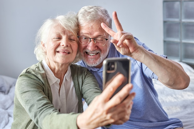 Elderly couple sitting on a couch taking photo on smartphone, posing at phone's camera, enjoying time at weekends. family, technology, age and people concept