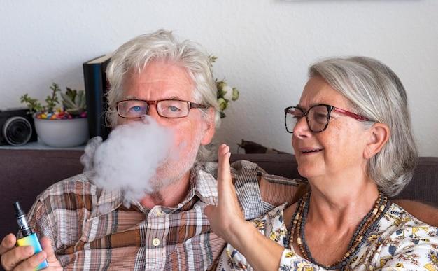 Пожилая пара сидит в помещении, муж курит электронную сигарету, а жену раздражает дым