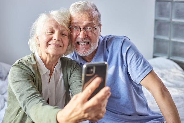 노인 부부는 스마트 폰에서 사진을 찍고, 전화에 포즈를 취하고, 주말에 시간을 즐기고 소파에 앉아 있습니다. 가족, 기술, 나이 및 사람들 개념