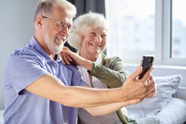 ソファに座ってスマートフォンで写真を撮ったり、スマートフォンのカメラでポーズをとったり、週末の時間を楽しんだりする老夫婦。家族、テクノロジー、年齢、人々の概念