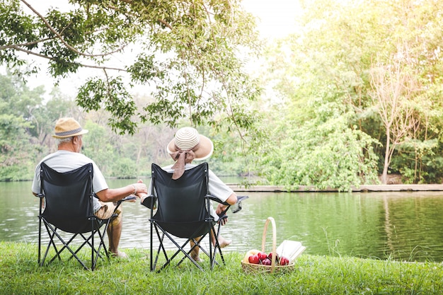 木陰のある庭で黒い椅子に座っている老夫婦パンと果物のピクニックバスケットがあります。高齢者のコミュニティ生活のコンセプト幸せと健康の創造。コピースペース