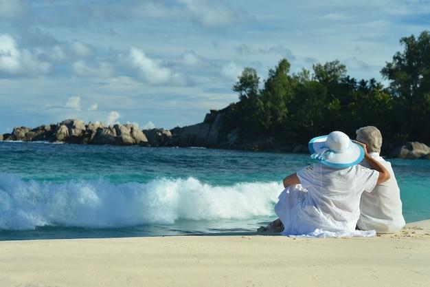 Пожилая пара сидит на берегу и смотрит на море