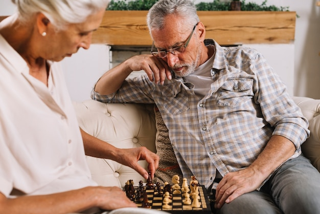 An elderly couple sitting on sofa playing chess