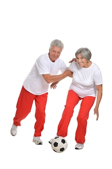 Elderly couple standing with a ball in a gym