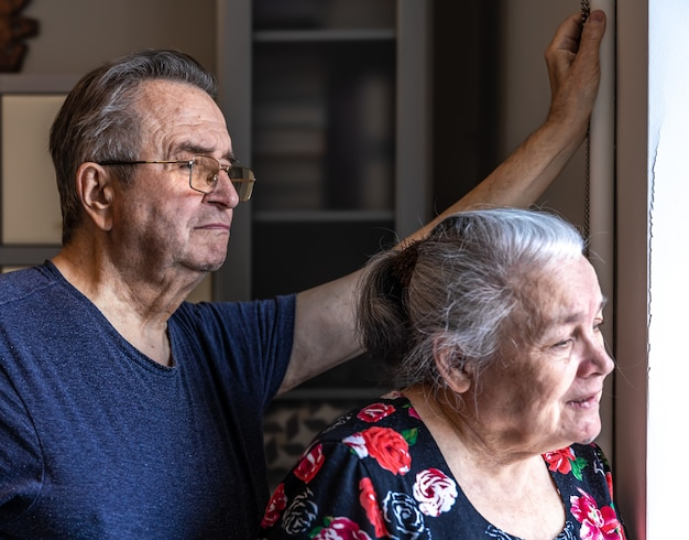 An elderly couple stands at the window and looks out at someone.