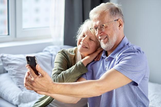 スマートフォンで写真を撮る老夫婦は、寝室に座って、笑顔で座っています。高齢者社会のライフスタイル技術の概念。男性と女性がウェルビーイングホームでソーシャルメディアを共有する