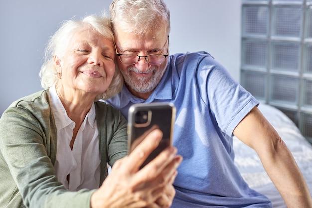 スマートフォンで写真を撮る老夫婦、寝室に座って、笑顔で座っています。高齢者社会のライフスタイル技術の概念。男性と女性がウェルビーイングホームでソーシャルメディアを共有する