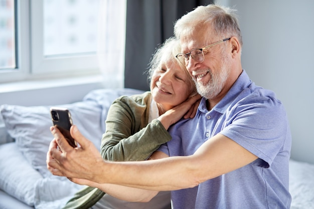 Elderly couple taking photo on smartphone, while sitting in bedroom, sit smiling. senior people society lifestyle technology concept. man and woman share social media together in wellbeing home