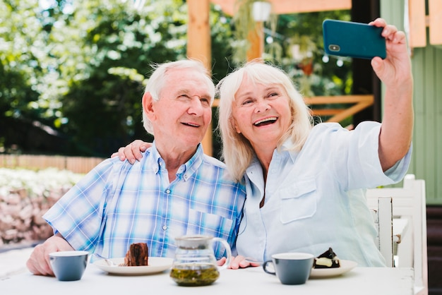 Elderly couple taking selfie smiling sitting on outside terrace