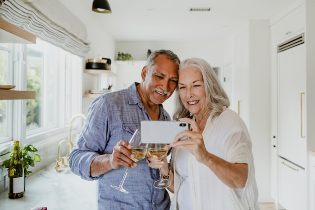 Elderly couple taking a selfie while having a wine