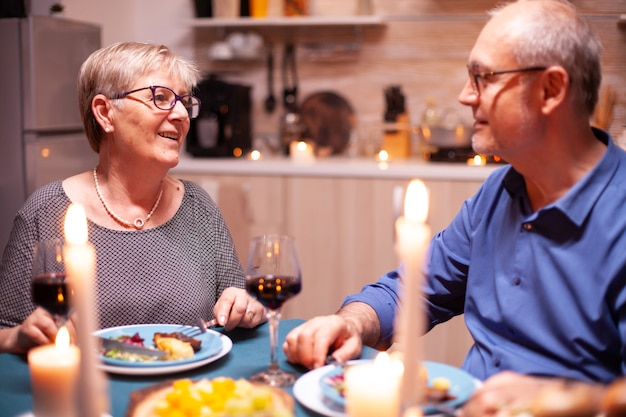 축제 저녁 식사 중 행복에 대해 이야기하는 노인 부부. 행복한 노인 부부는 아늑한 주방에서 함께 식사를 하고 기념일을 축하하며 식사를 즐기고 있습니다.