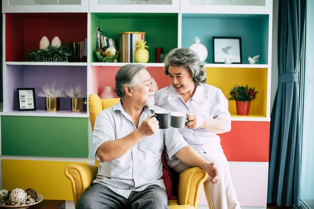 Elderly couple talking together and drinking coffee or milk